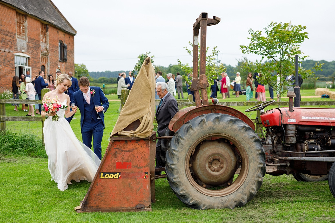 bride and groom get into the godwick tractor