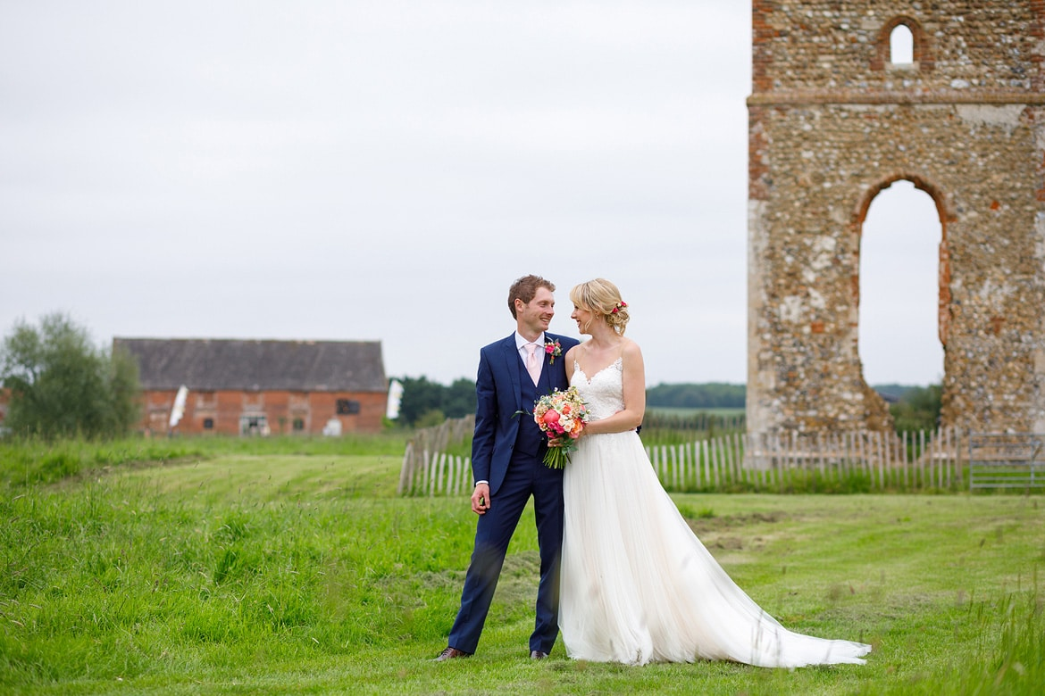 bride and groom in front of godwick barn and the ruins