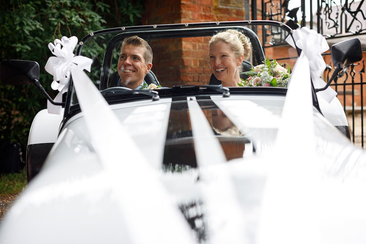 bride and groom in their robin hood wedding car