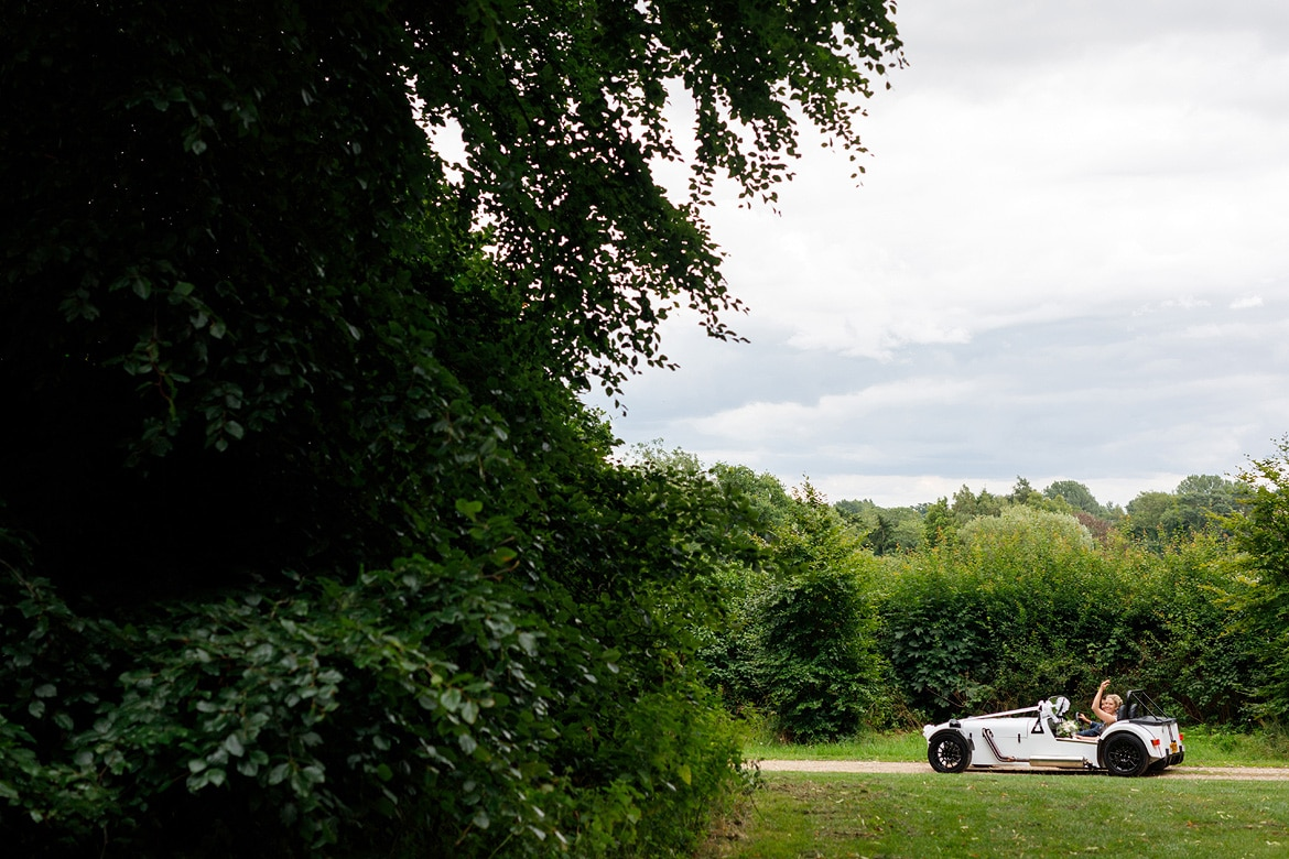 the wedding car drives through the grounds of gressenhall
