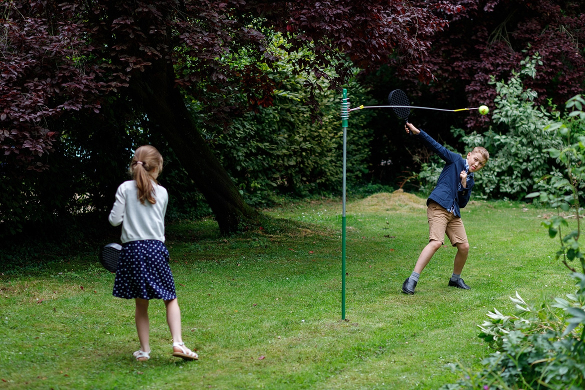 children play swingball in the garden