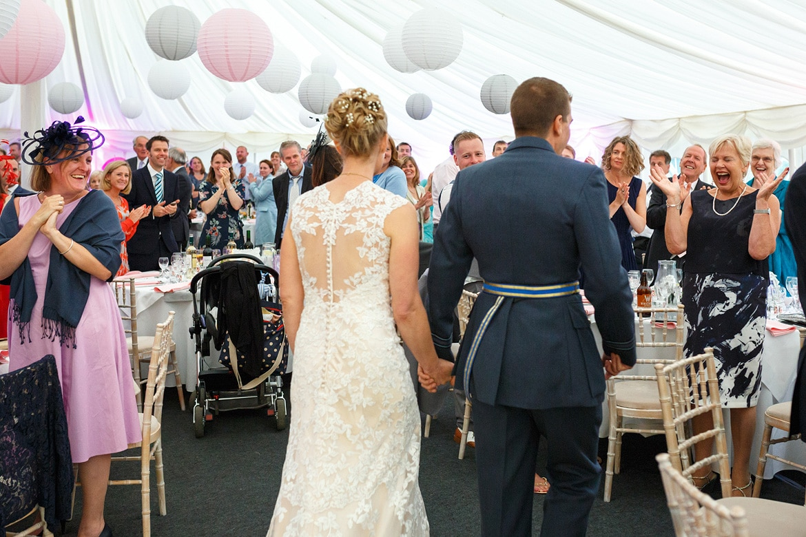 bride and groom enter the marquee for the wedding breakfast
