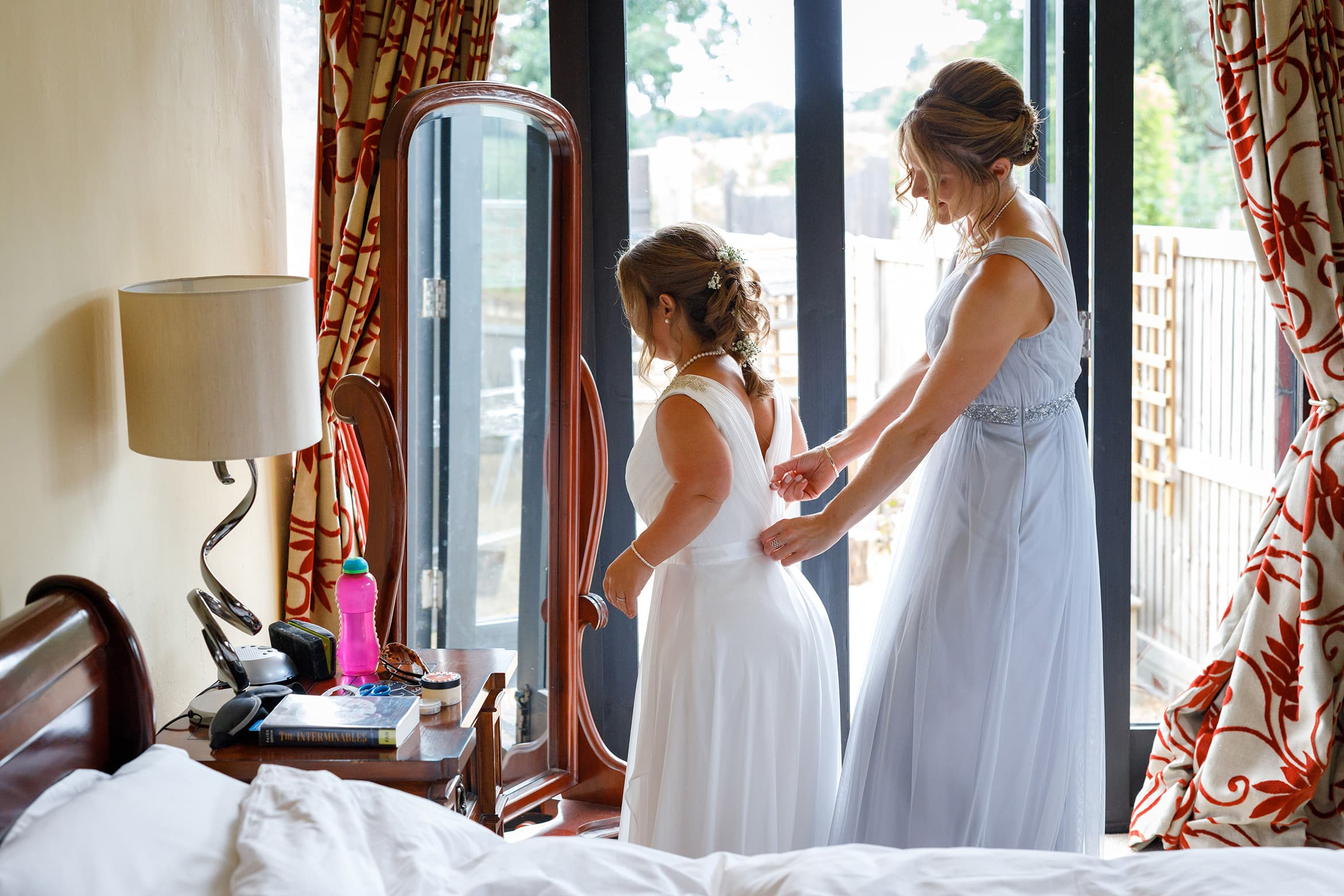 the brides sister helps her into her dress