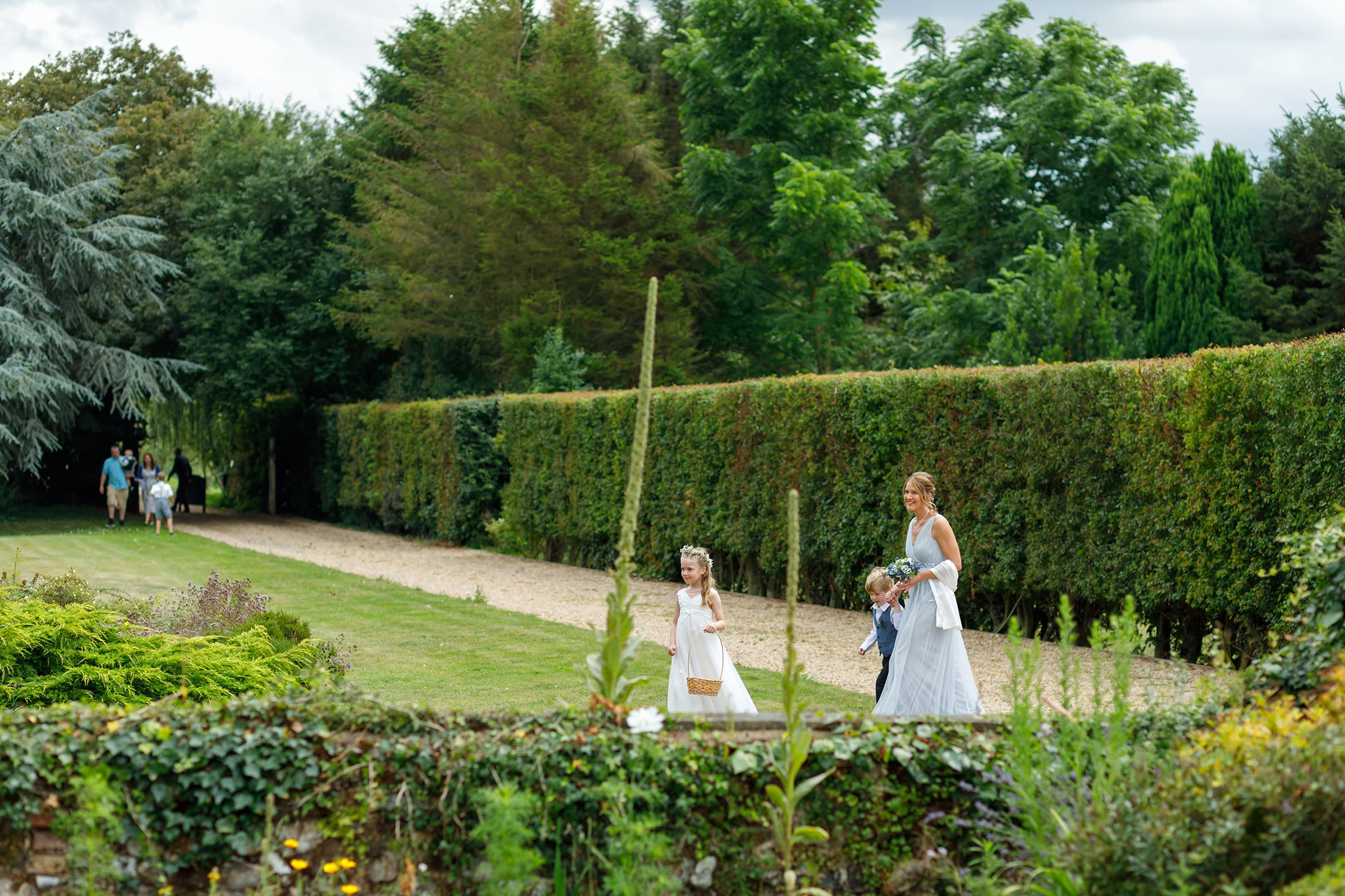 the bridesmaid and flowergirl walk across the lawn