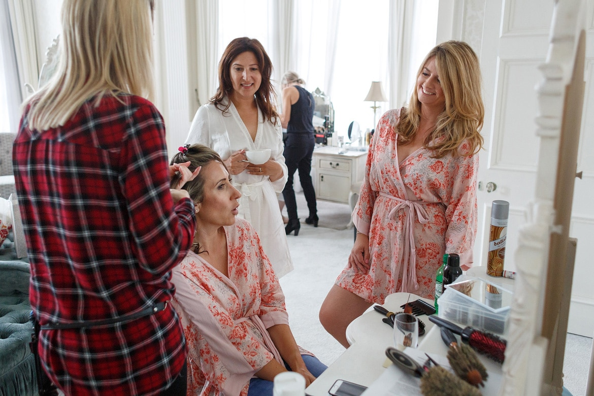 the bride and her bridesmaids getting ready