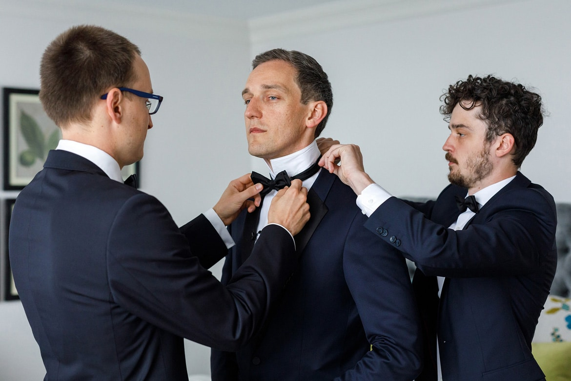 the groomsmen help the groom get ready