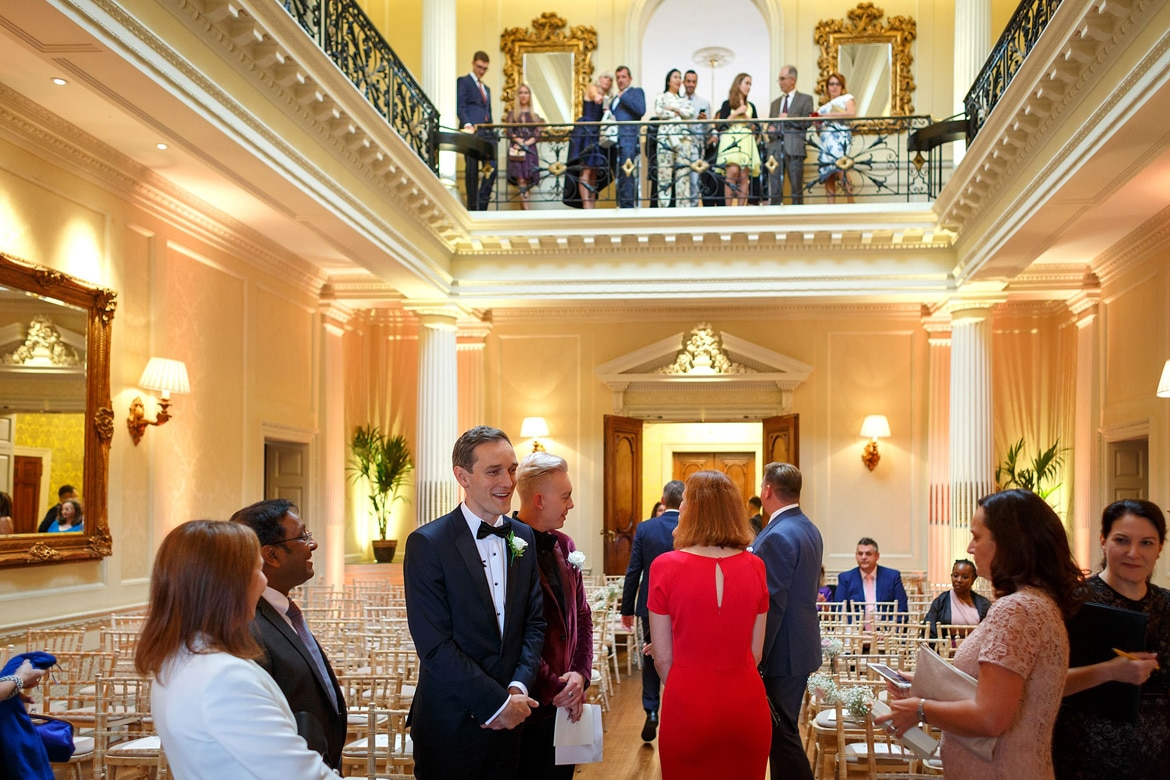 the groom greets wedding guests in the centre hall at hedsor house