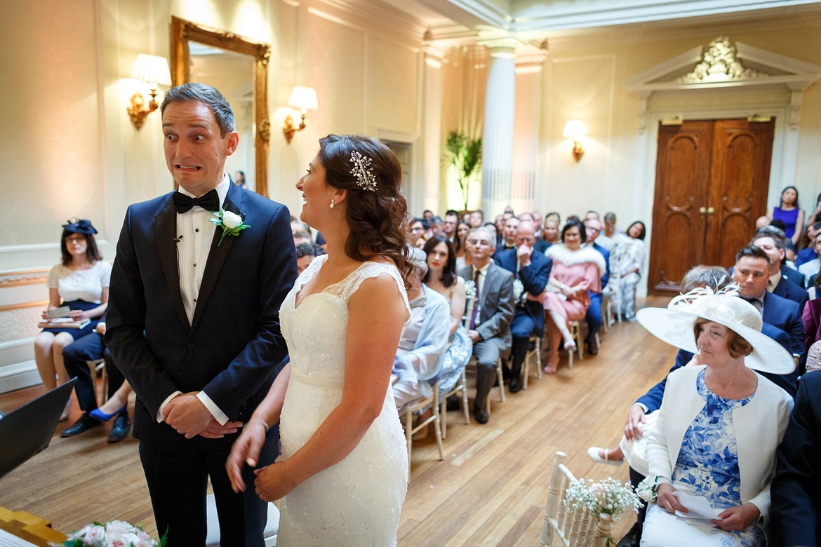 the groom pulls a face during his hedsor house wedding ceremony