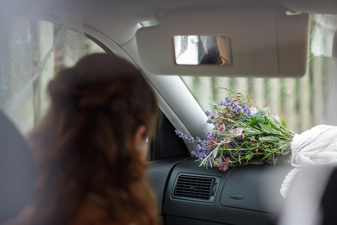 the brides bouquet on the dashboard of the wedding car