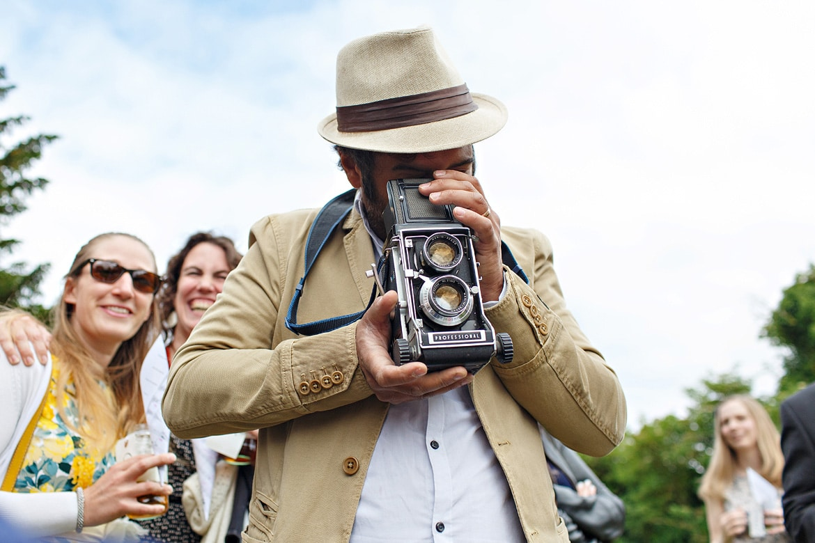 a wedding guest takes a photo on a vintage camera