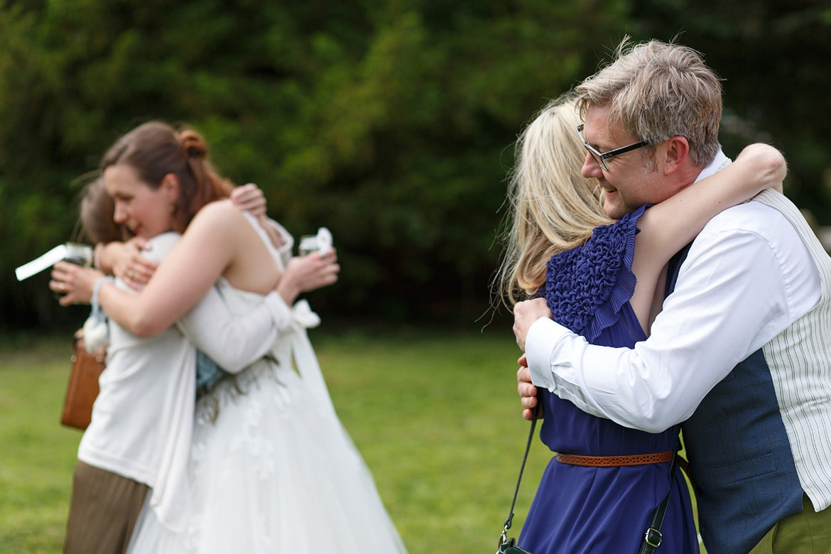 a double hug for the bride and groom