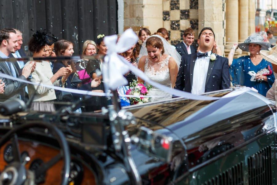 bride and groom walking through confetti after their kings lynn wedding ceremony