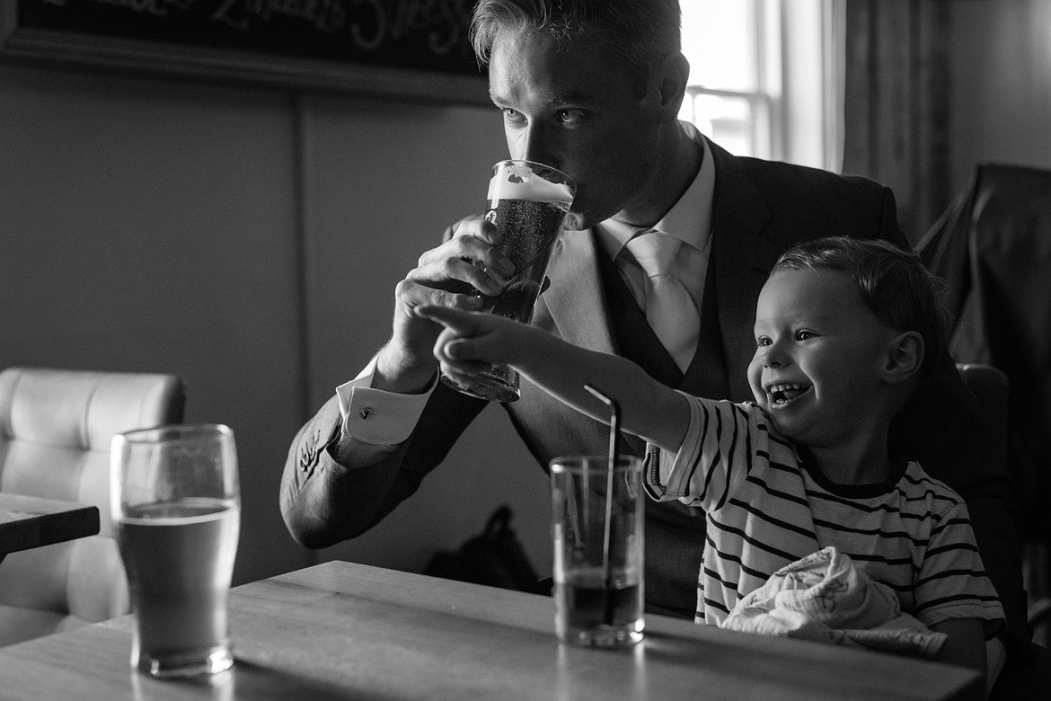 the groom takes a drink with his son on his lap