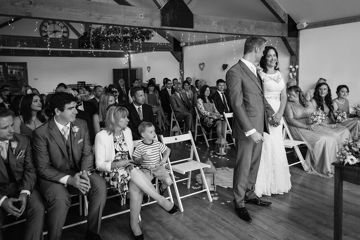 bride and groom peek nervously at each other during their maidens barn wedding ceremony