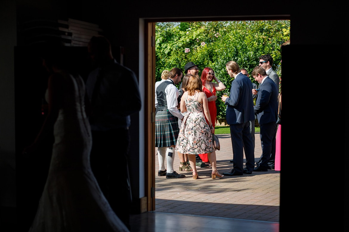 looking out of the barn at a group of wedding guests