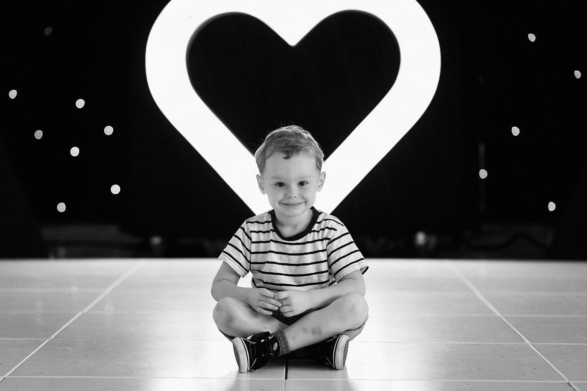 the bride and grooms son sitting in front of a love heart