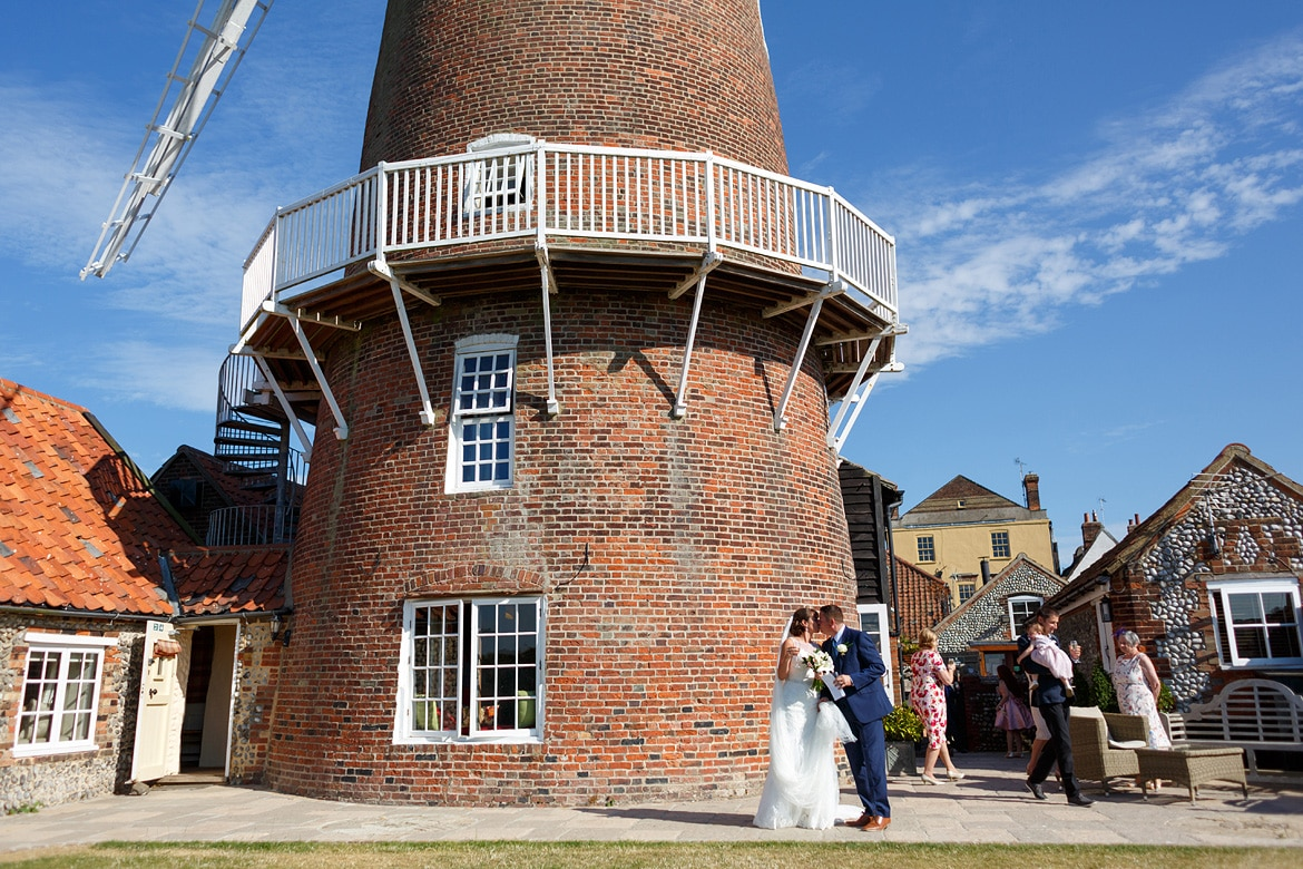 kisses outside a cley windmill wedding