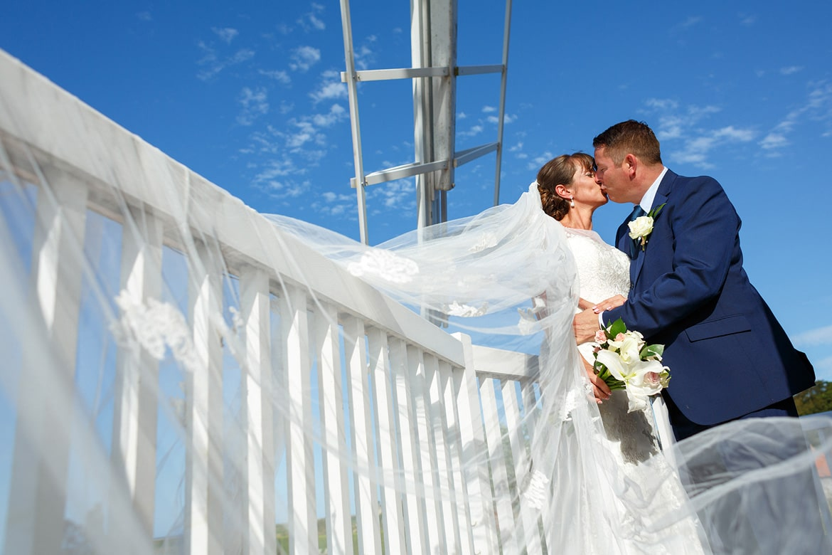 bride and groom kiss on the balcony of cley windmill