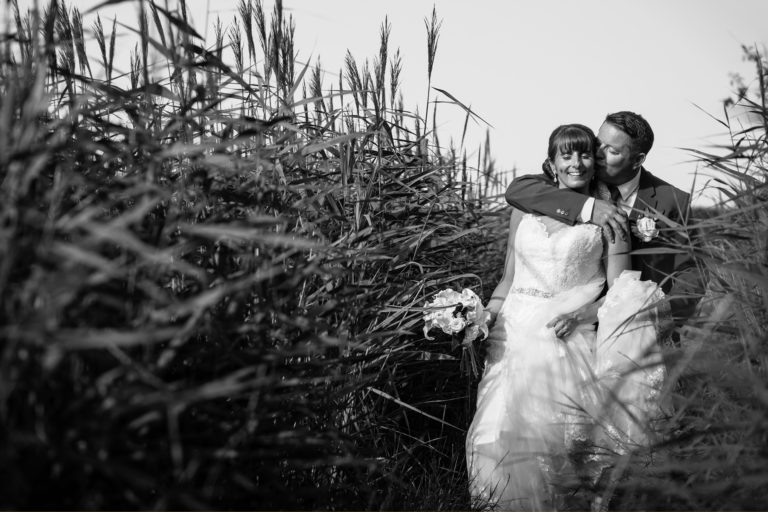 eva and mark in the reeds at their cley windmill wedding