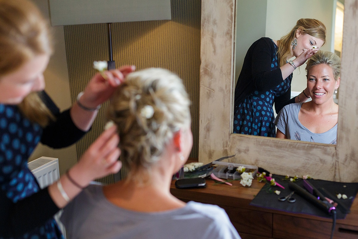 a bridesmaid having her hair finished at godwick hall