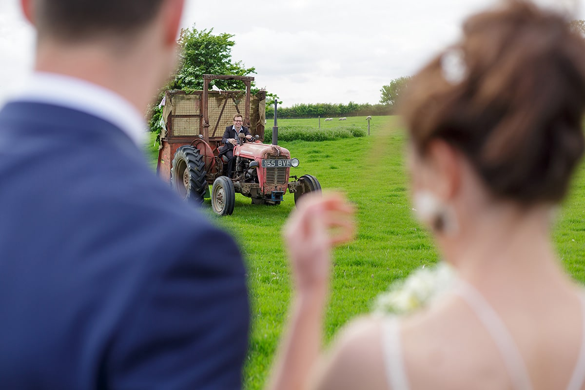 bride and groom wait for the tractor