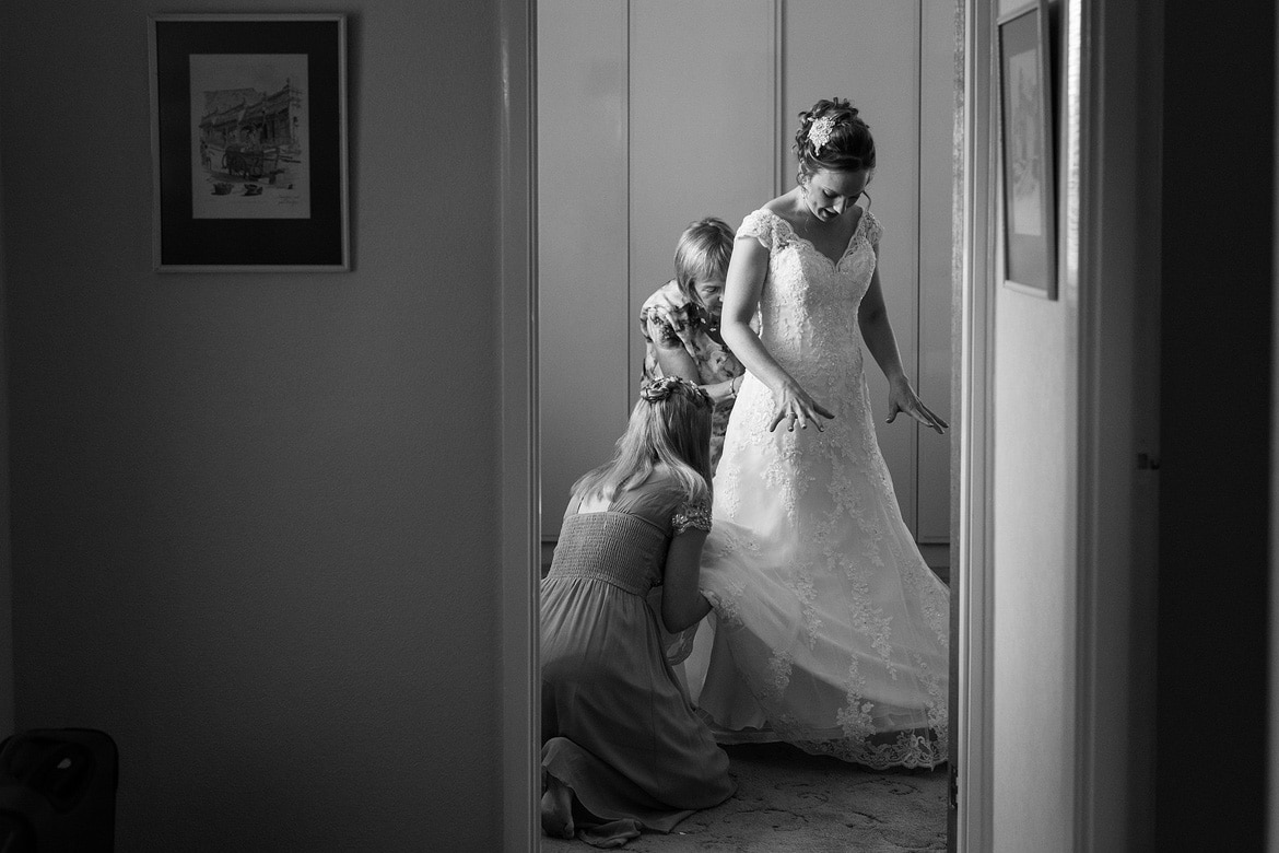 the bride puts her dress on in the bedroom