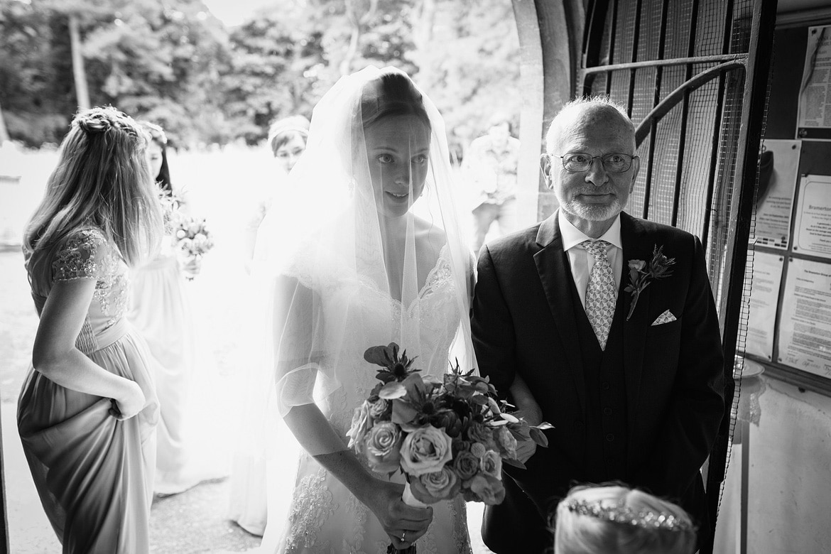 the bride and her father in the porch of bergh apton church