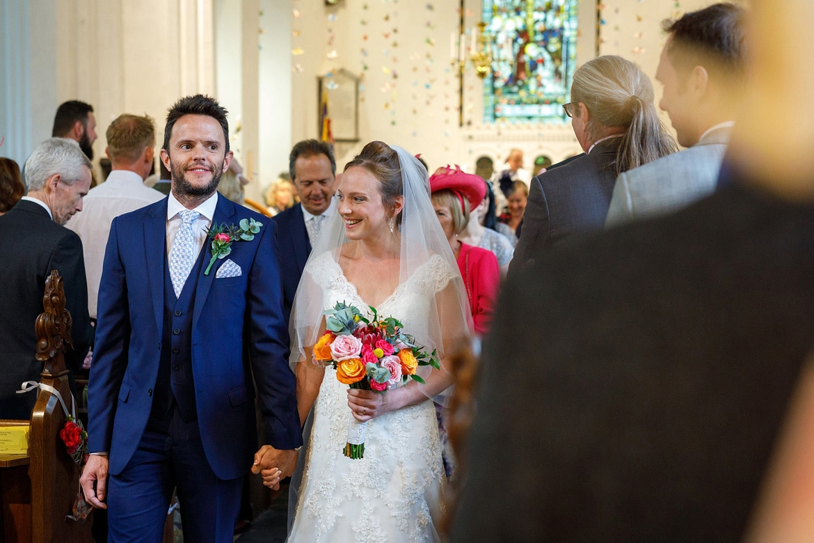 kate and daniel walk back down the aisle at bergh apton church