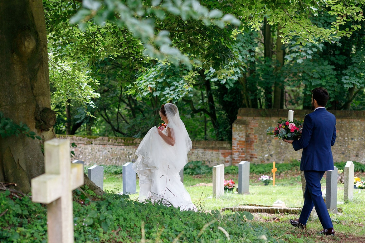 bride and groom walk through the churchyard