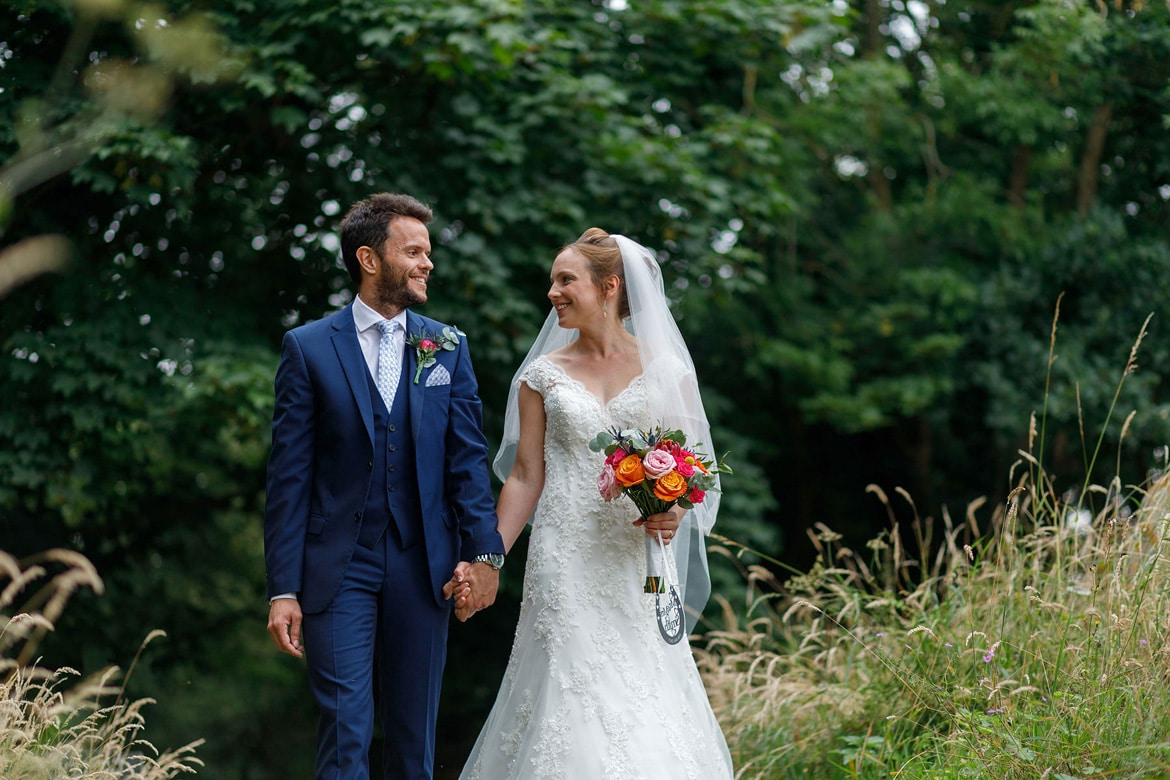 bride and groom walk through bergh apton churchyard