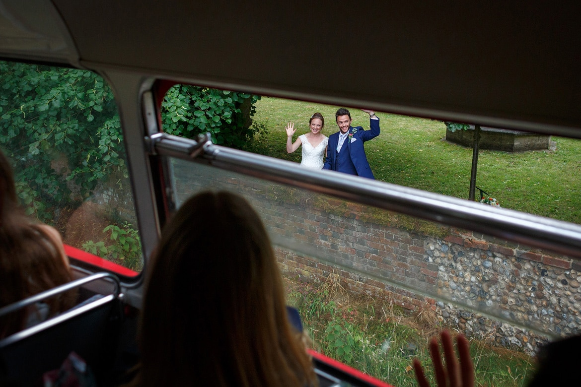 kate and daniel wave off their guests in the routemaster bus