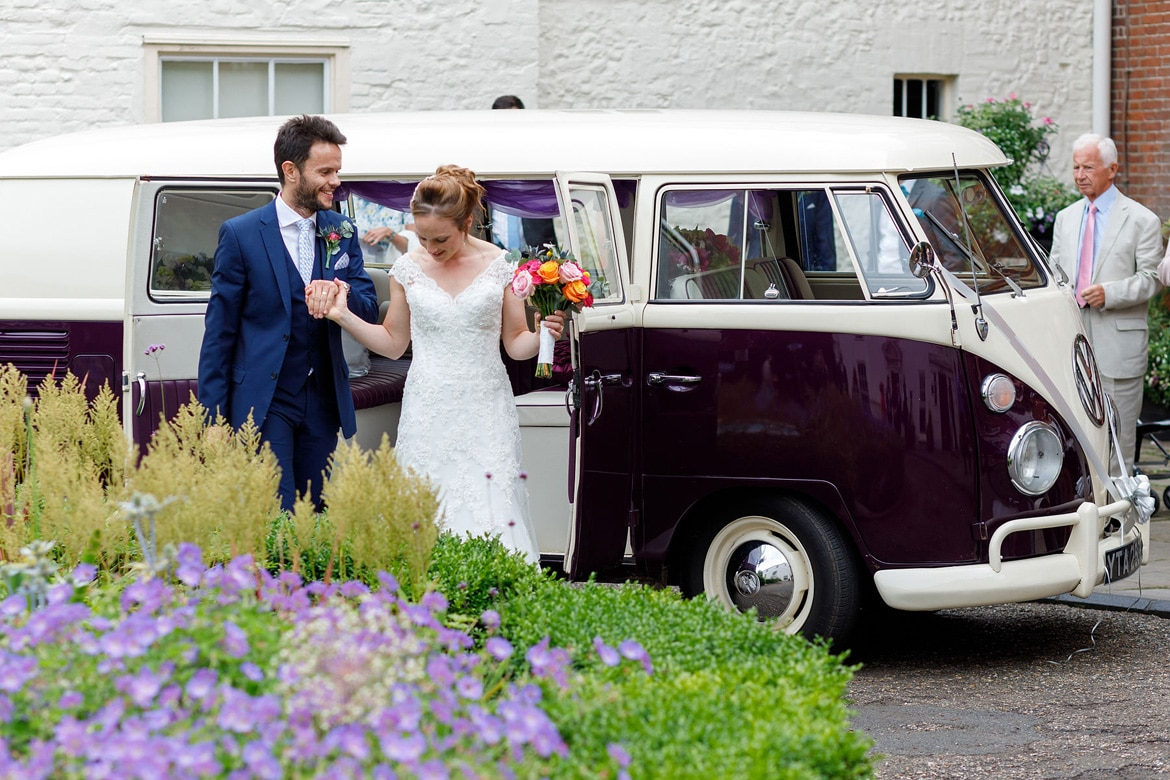 kate and daniel leave their campervan wedding car