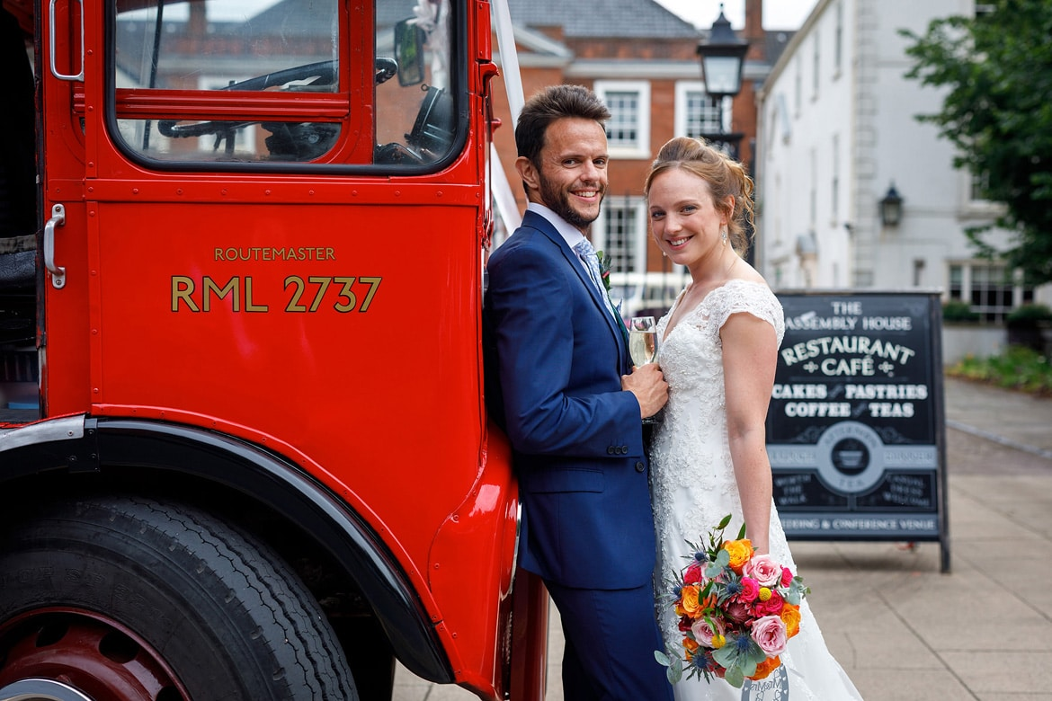 bride and groom pose with the routemaster bus outside the assembly house norwich
