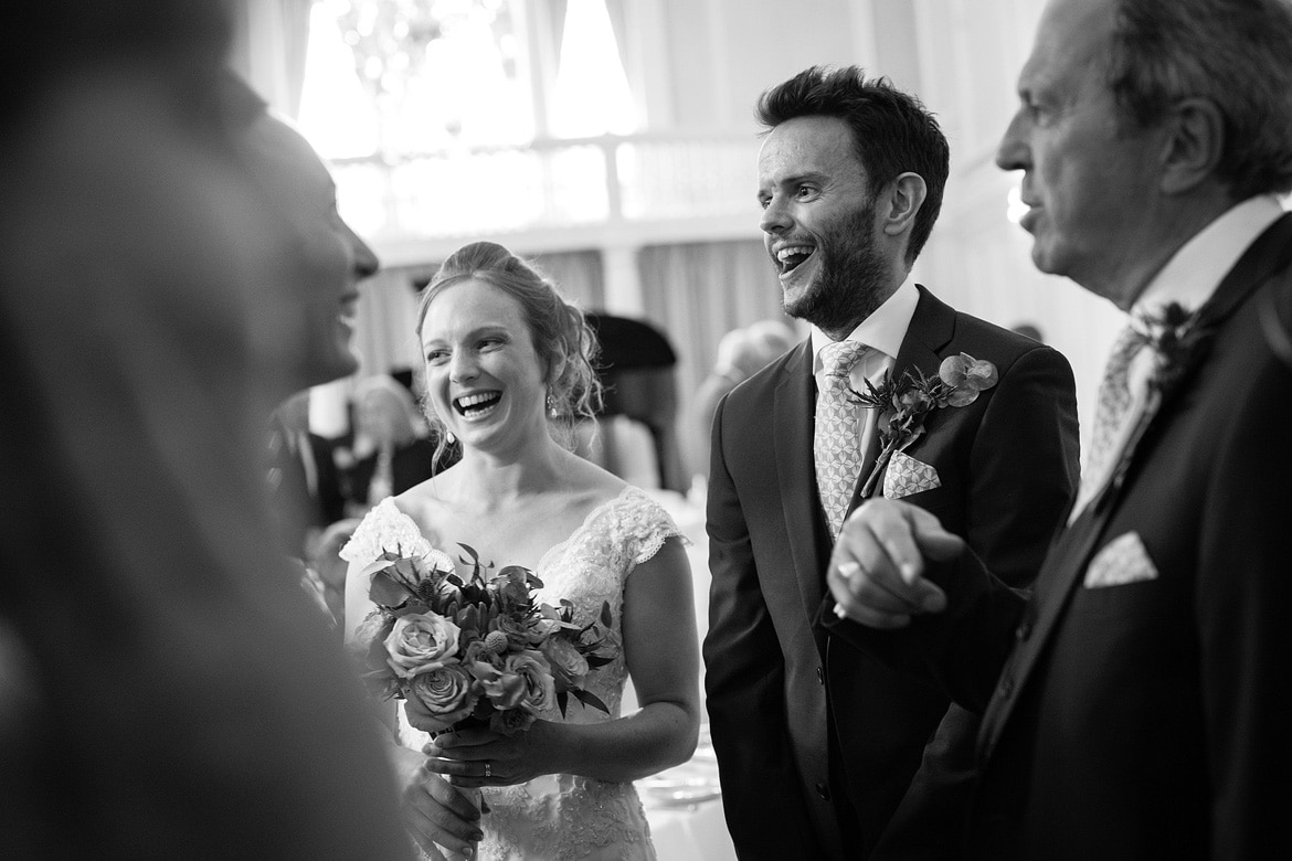 bride and groom laugh in the receiving line