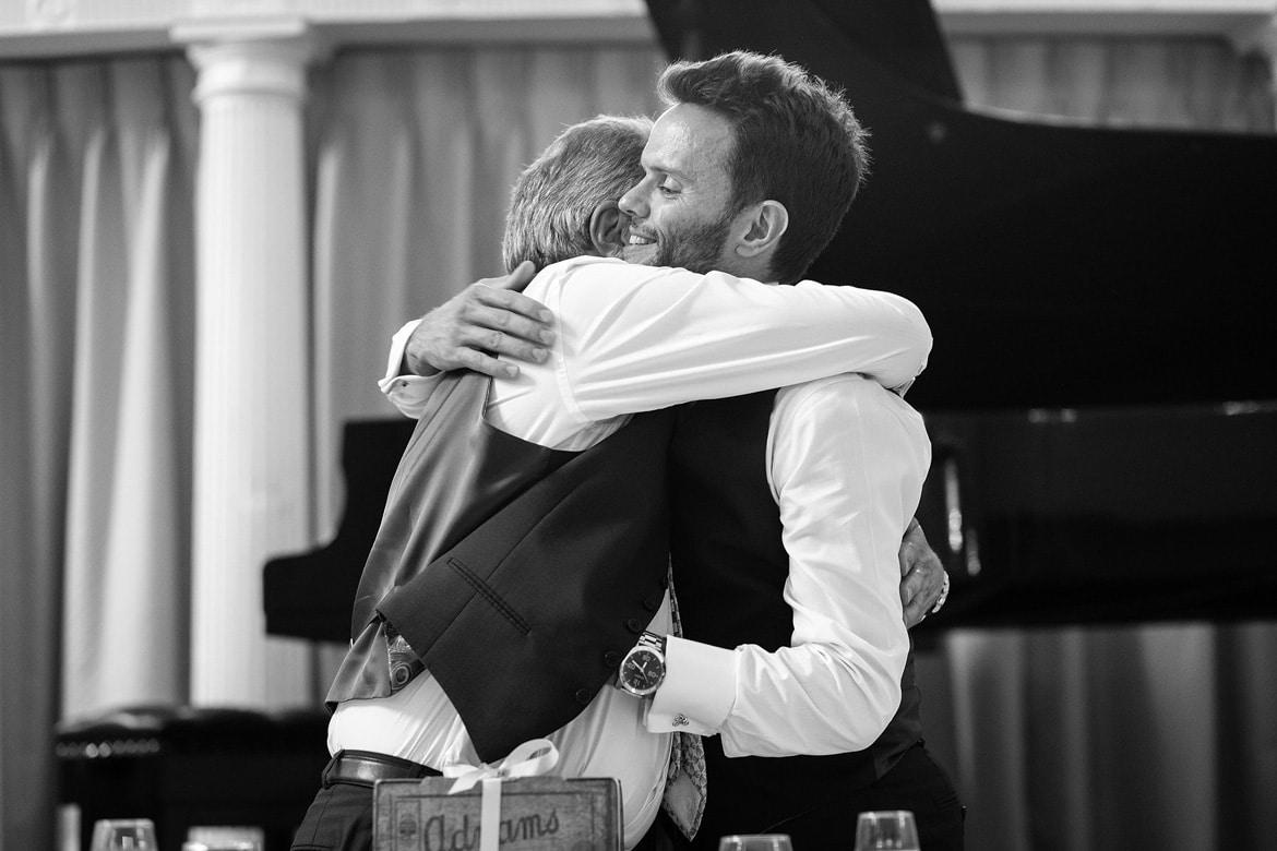 groom and dad hug