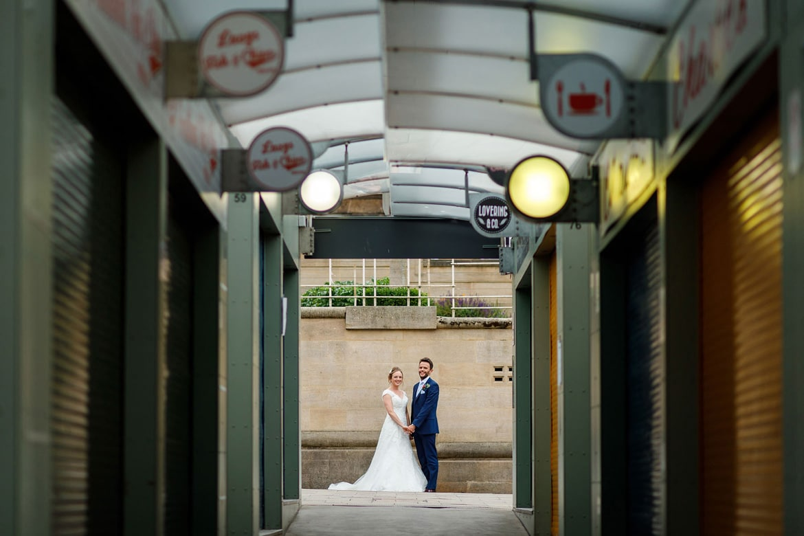 bride and groom viewed from inside norwich market