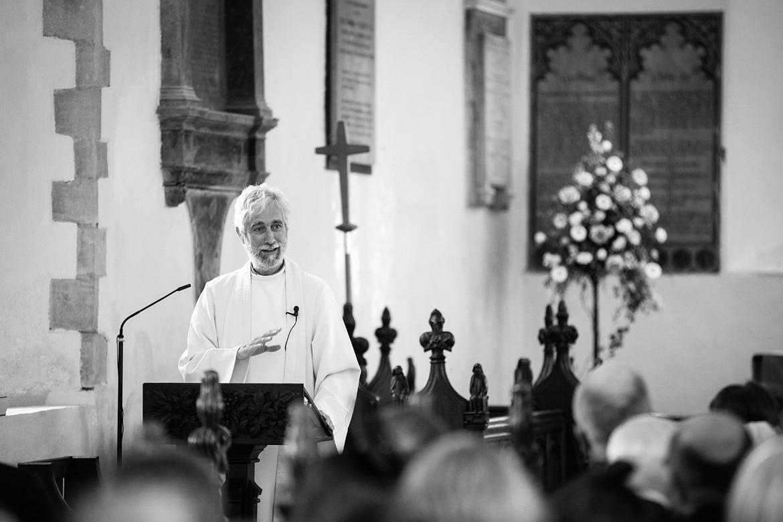 the vicar gives his sermon at an old buckenham church wedding