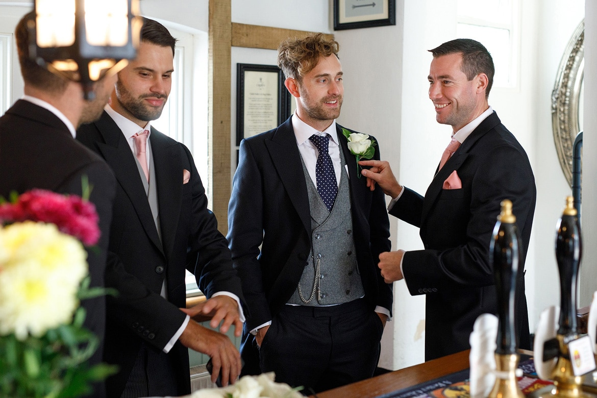 an usher pins on the grooms buttonhole
