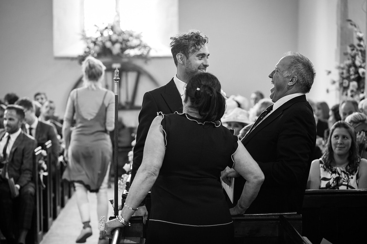 the groom enjoying a moment with guests inside st marys sydenham