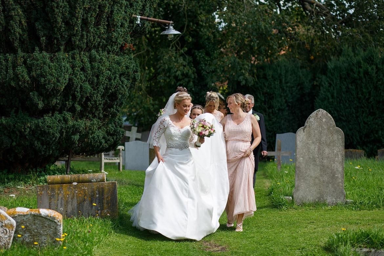bride and bridesmaids walk through the churchyard