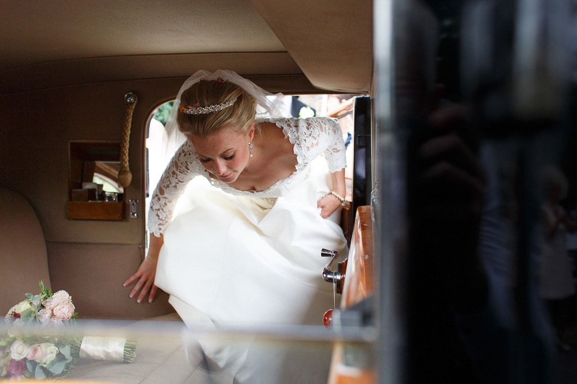 the bride gets into the wedding car