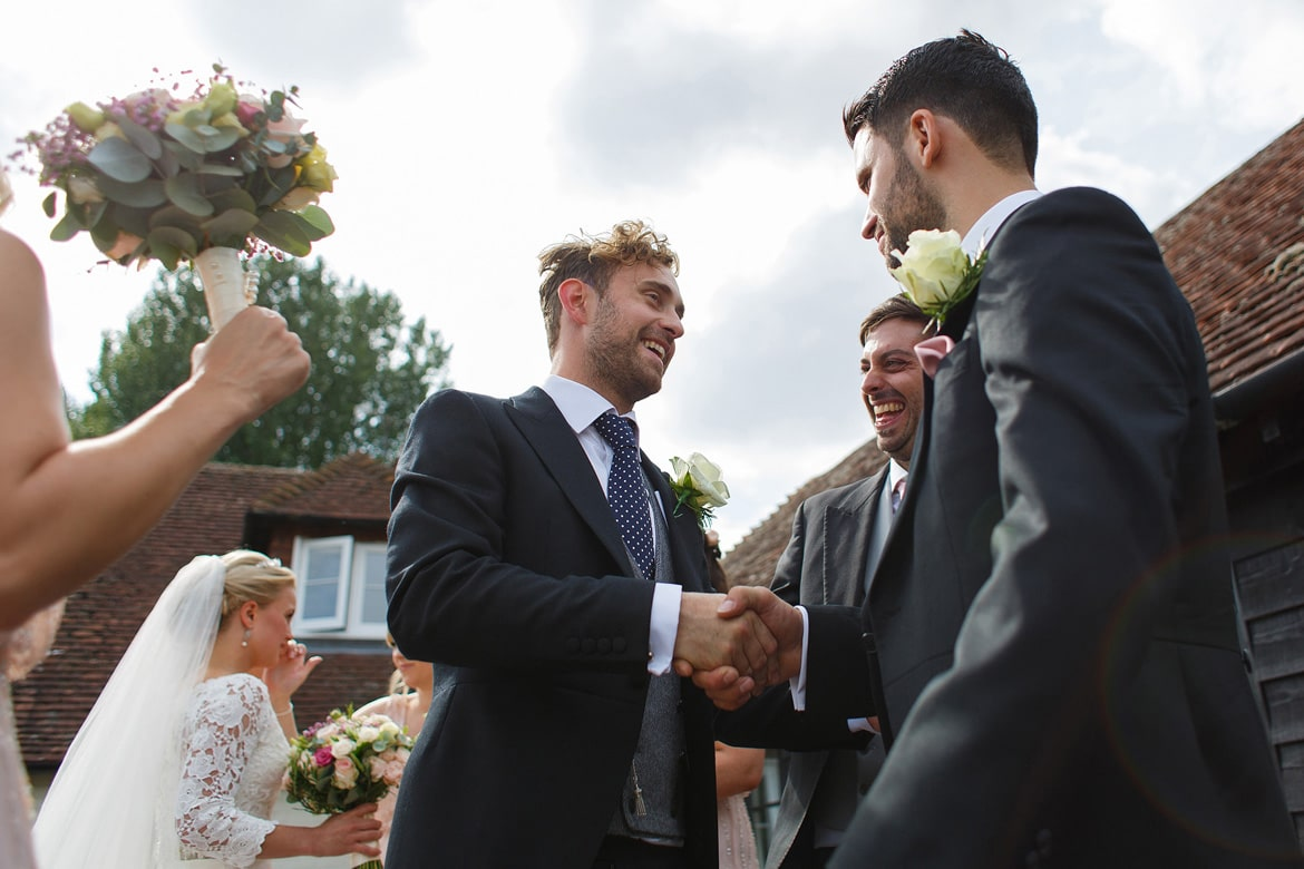 the groom is greeted by his friends