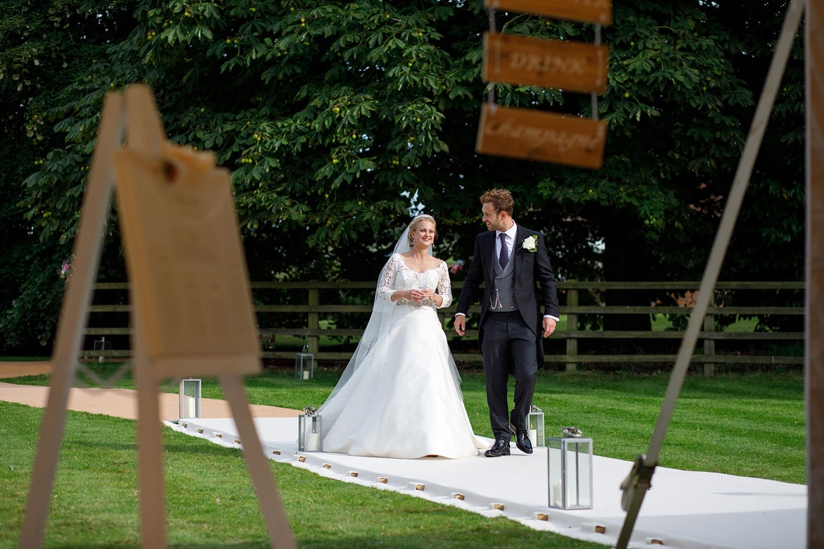 bride and groom walk to the marquee