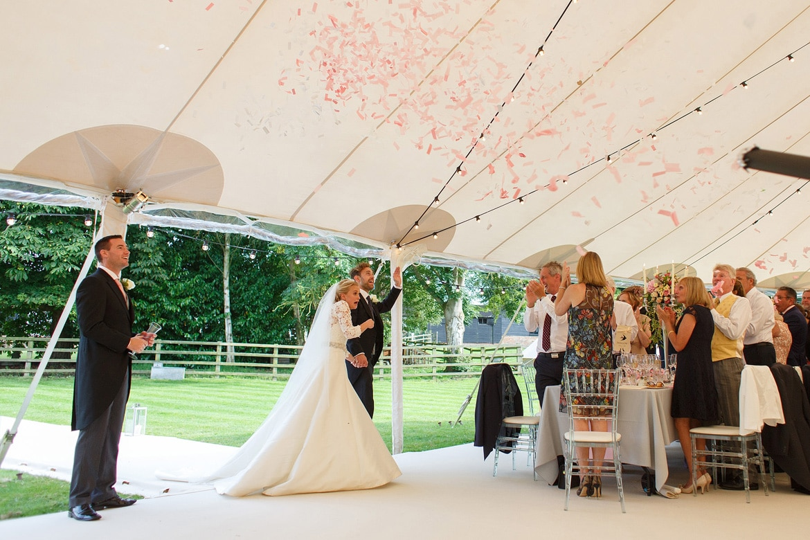 confetti cannons as the bride and groom enter the marquee