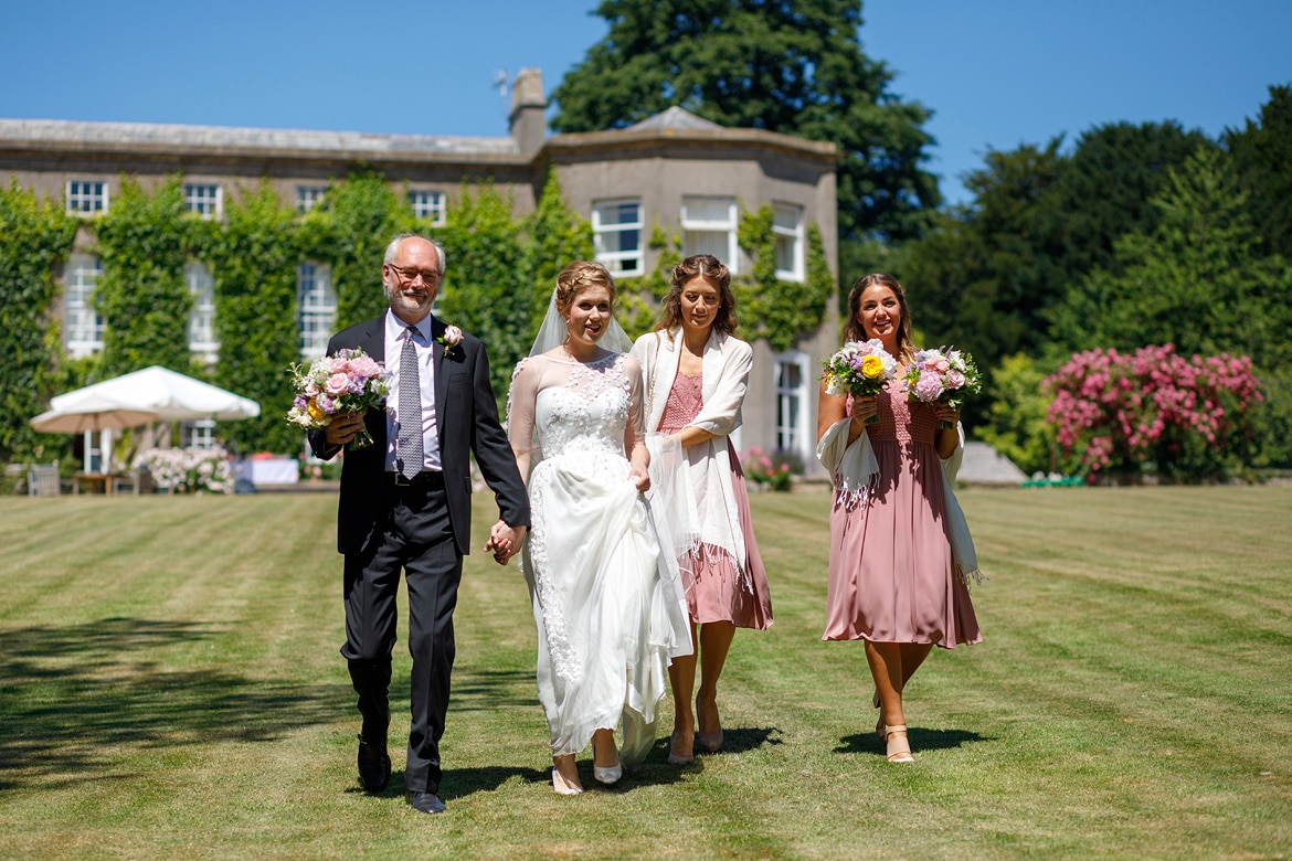the bride walks down pennard house lawn with her father and bridesmaids