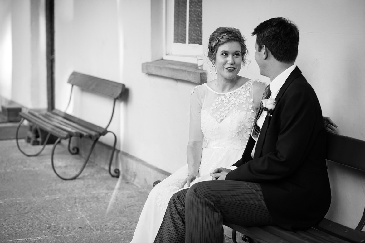 bride and groom sitting at the front of pennard house