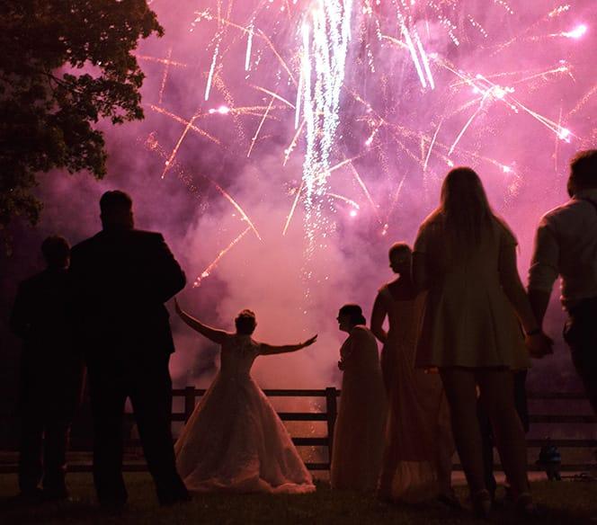 bride dancing in front of wedding fireworks