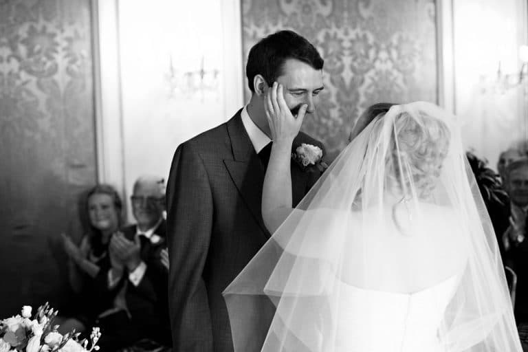 bryony wipes a tear from richards face during their somerleyton hall wedding ceremony