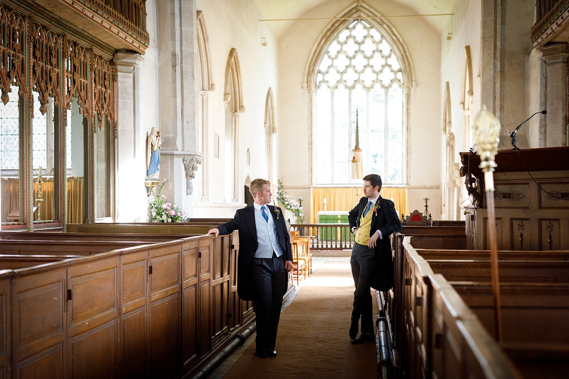the groom and his best man chat inside dennington church
