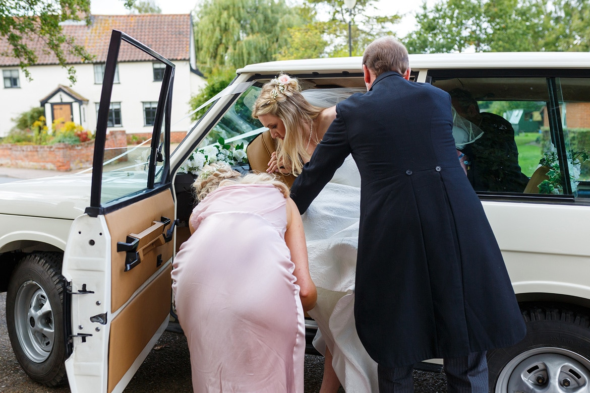 the bride is helped out of the car
